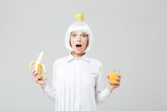 Wondered young woman with apple on her head holding banana. And glass of juice over white background Royalty Free Stock Image