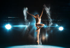Wonderful adult ballerina posing on stage against spotlights Stock Photo