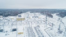 Electrical transmission station among snow and woods. Wonderful aerial view powerful electrical transmission station among snow and woods on frosty winter day stock footage
