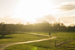 Wonderful afternoon sky with people riding a bike in the distance on the path green warm lands. stock photos