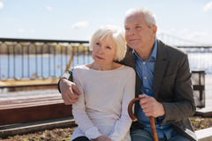 Wonderful aging couple spending free time outdoors. Pay more attention to each other. Charmed beautiful happy people looking at balloons in the sky sitting calm royalty free stock image