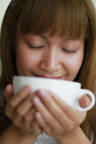 Wonderful Aroma of Coffee. A young lady smelling the wonderful aroma of her coffee drink. (Shallow depth of field Royalty Free Stock Photos