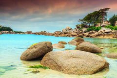 Wonderful Atlantic ocean coast with granite stones, Perros-Guirec, France. Stunning rocky beach with pink granite stones and wonderful green gardens on the coast Royalty Free Stock Images