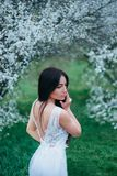 Wonderful attractive lady with dark black long hair and blue eyes looking down, stands beside blooming magnolias stock photography
