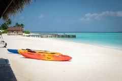 Three canoes on the white sand beach, stone pier on turquoise lagoon in Maldives royalty free stock photo