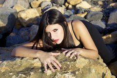 Wonderful beautiful female model posing with night dress laying on rocks looking Stock Photo