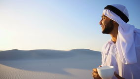 Wonderful beginning of morning for Arabian Sheikh guy in middle of huge desert over cup of coffee against blue sky in. Portrait  confident and happy male Arabian stock video footage