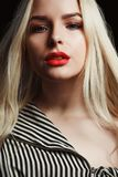 Wonderful blonde lady with bright makeup and long hair posing over a black background stock photo