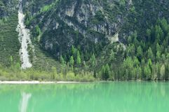 The wonderful Braies lake in the Dolomites in spring with the mountains still covered in snow. Italy is a country with many wonderful places and the Dolomites Stock Image