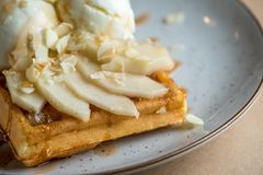 Wonderful breakfast or dessert - vanilla ice cream with caramel sauce on Belgian waffle with slices of ripe pear, top Stock Image