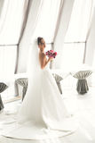 Wonderful bride with a luxurious white dress posing in the old town royalty free stock image