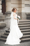 Wonderful bride with a luxurious white dress posing in the old town royalty free stock images