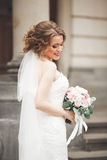 Wonderful bride with a luxurious white dress posing in the old town royalty free stock photo