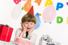 Wonderful cake. Portrait of surprised lad touching his cheeks and looking at burning candles on birthday cake Stock Image
