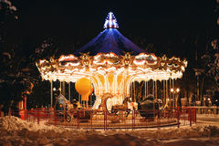 Wonderful carousel in park at night in winter Stock Images