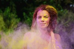 Wonderful caucasian model with curly hair posing in a cloud of p. Wonderful caucasian woman with curly hair posing in a cloud of purple and yellow Holi paint royalty free stock photo