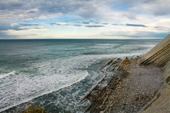 Wonderful coastline with waves on ocean in colorful sky with clouds Stock Photography
