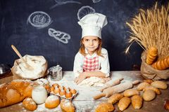 Adorable little girl in chef hat making dough. Wonderful content little girl in checkered apron and hat of chef standing at table and making bread dough looking royalty free stock photos