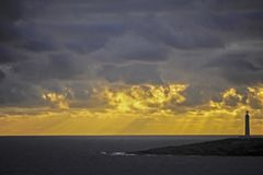 Wonderful Contrasting Colours of Bright Yellow and Grey Clouds, behind a Light-House. Gray Ocean at Cape Leeuwin Light-House, with a Yellow Sunset. Wonderful stock photo
