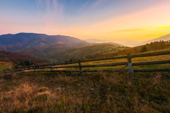 Wonderful countryside scenery in autumn. Beautiful sunrise in mountains. wonderful countryside scenery in autumn. fence along the rural fields. fog in the royalty free stock photos
