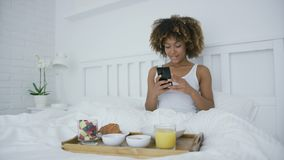 Woman with smartphone in bed having meal. Wonderful curly woman sitting on cozy bed and taking photo of served amazing breakfast on wooden tray using smartphone stock video footage