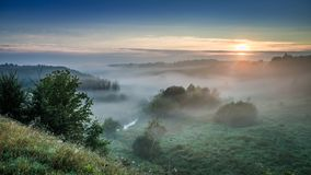 Wonderful dawn at foggy valley in autumn royalty free stock photography