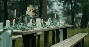 Wonderful decor for first romantic date in charming mysterious forest: leaves, candles, flowers and white two-tiered stock footage