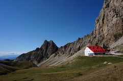 Wonderful dolomite mountains scenry and alpine refuge with red roof stock photo