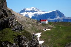 Wonderful dolomite mountains scenry and alpine refuge with red roof / sella and boe peak in the background Stock Photography