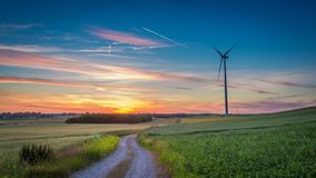 Wonderful dusk over field with wind turbines Royalty Free Stock Image