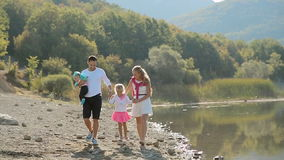 Wonderful family walks along the shore of the pond stock video