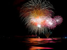 Wonderful fireworks lighting ocean`s water Stock Image