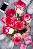Composed of the roses and mobile phone on the back of a blurry background stock photo
