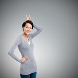Wonderful girl gestures hand horn Royalty Free Stock Photo