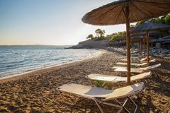 Wonderful Greece - beach : transparent water . sand and straw awnings. Mediterranean sea.    Sunny  Beautiful morning. Greek  island Spetses stock image
