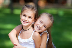 Wonderful happy girls standing on the lawn. Stock Photo