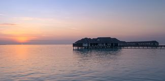 Incredible orange sunset over the turquoise lagoon, with water bungalows in Maldives stock image