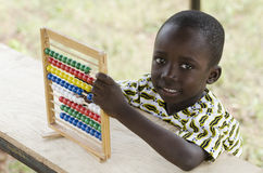 Wonderful image of an African schoolboy playing and learning. Little african boy counting on abacus Royalty Free Stock Images