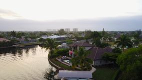 Wonderful 4k aerial drone panorama landscape view on small tropical luxury resort town deep blue calm canal river water stock video