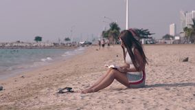 Wonderful lady with bare feet in sand sits on ocean beach. Wonderful lady with bare legs and feet in sand sits on beach and reads book near ocean foaming waves stock footage
