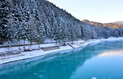 The wonderful lake of Auronzo, frozen in the middle of winter, amidst the immense forests of the Dolomites stock images
