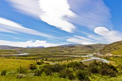 Wonderful landscape in south america in strong wind. With beautiful clouds formation and river in a valley royalty free stock photo