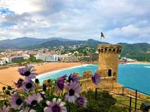 Wonderful landscape in Tossa de Mar, Spain. Medieval tower, beach, sea and flowers. Wonderful landscape, medieval tower, beach, sea, flowers, tourism and shore royalty free stock photography