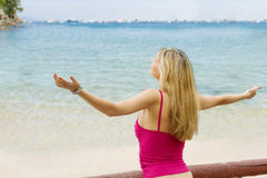 Wonderful life. Fashion portrait of young blond female in act to enjoy the life with open arm on beach Stock Photos