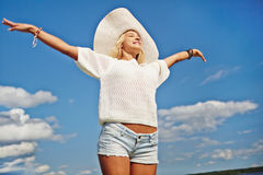 Wonderful life. Happy girl with outstretched arms against cloudy sky Stock Photos