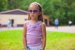 Wonderful little girl in sunglasses walking at Stock Photo