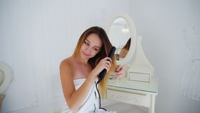 Charming Female Aligns Hair Using Curling Irons and Hair Done, Sitting on Chair. Wonderful Long-Haired Girl Cares For Hair and Equates Strands Using Styler Hair Royalty Free Stock Photography