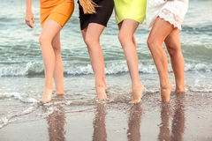 Wonderful long-legged women are posing on the sea background. A cute sports women`s legs. Beautiful girls on a tropical Stock Image