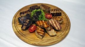 A wonderful meat dish cooked on a barbecue with ribs juicy and leaves of lettuce and laid out on wood stock photography