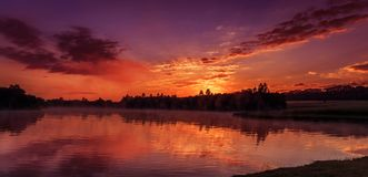 Wonderful misty morning. majestic red sunrise over the foggy lake stock photography